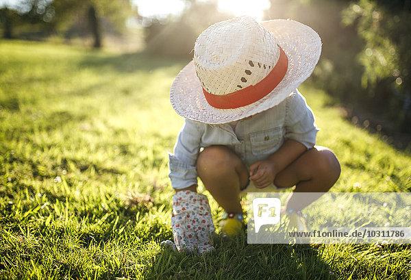 Little girl wearing straw hat crouching on a meadow