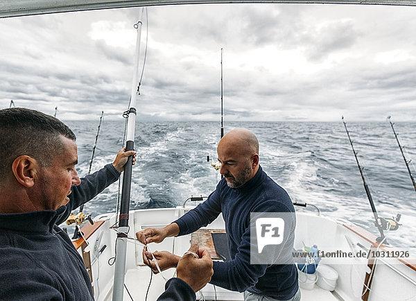 Spanien  Asturien  Fischer auf dem Fischerboot auf dem Kantabrischen Meer