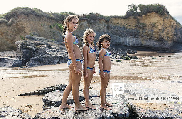 Spain  Colunga  three girls standing in a row on the beach