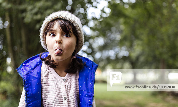 Portrait of little girl sticking out her tongue