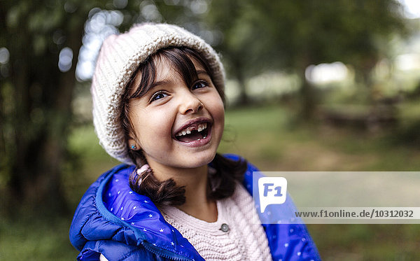 Portrait of laughing little girl with tooth gap