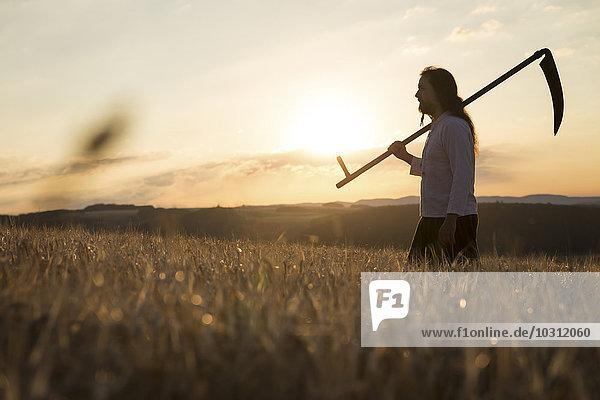 Bio-Bauer mit Sense im Gerstenfeld bei Sonnenaufgang
