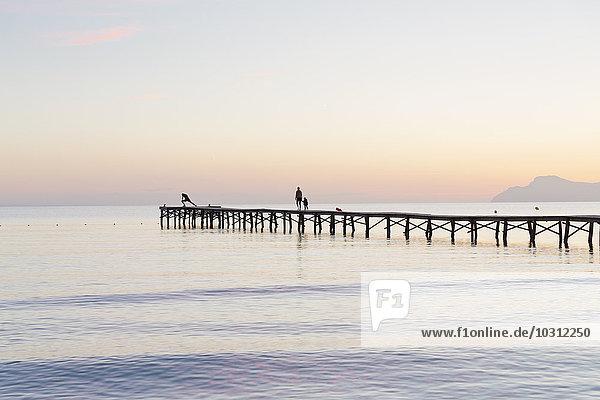 Spanien  Balearen  Mallorca  Menschen  die im Morgenlicht auf einem Steg laufen