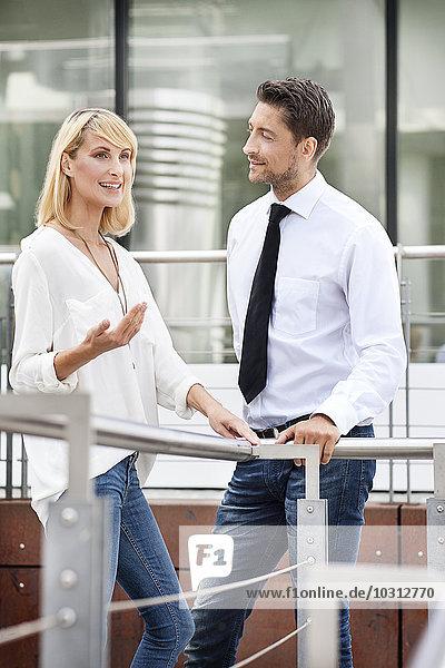 Geschäftsfrau  die ihrem Geschäftspartner etwas erklärt
