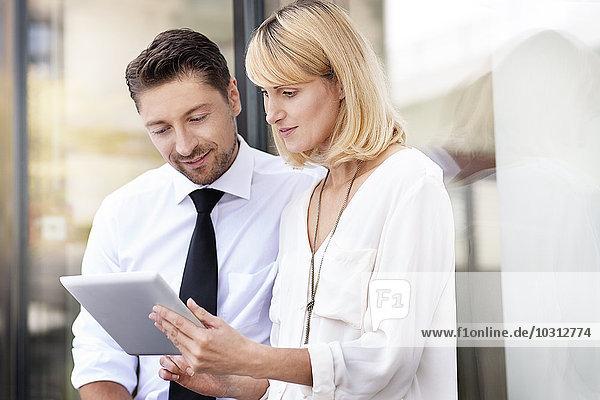 Zwei Geschäftspartner auf der Suche nach einem digitalen Tablett