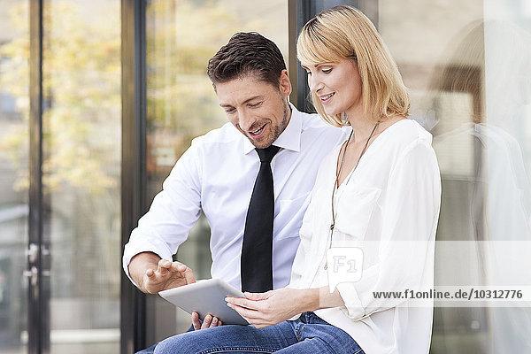 Zwei Geschäftspartner sitzen Seite an Seite mit digitalem Tablett