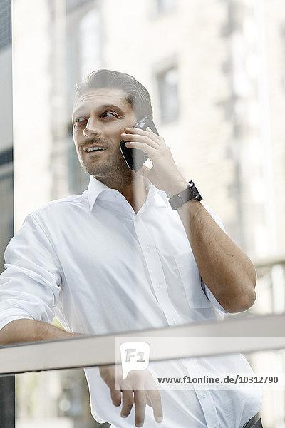 Geschäftsmann  der sich beim Telefonieren mit dem Smartphone an die Fensterscheibe lehnt