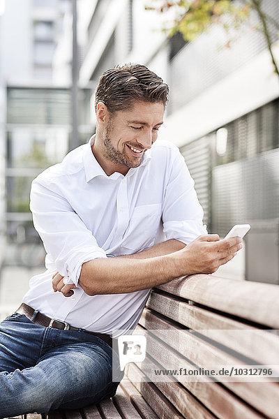Porträt eines lächelnden Mannes auf einer Holzbank mit Blick auf sein Smartphone