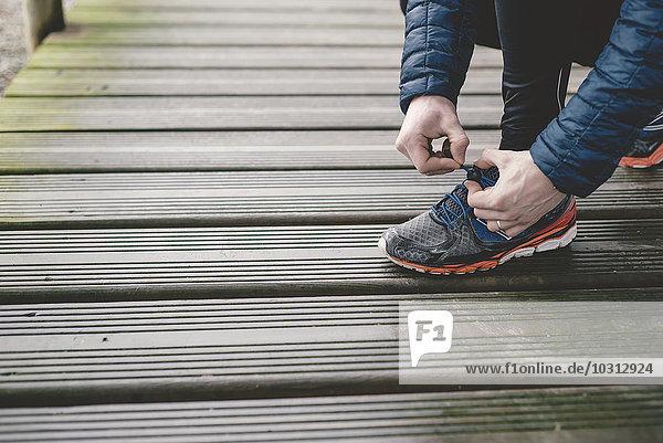 Jogger bindet seine Turnschuhe auf einen Holzboden.