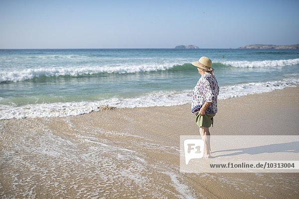 Spanien  Ferrol  Seniorin am Strand stehend mit Blick auf die Ferne