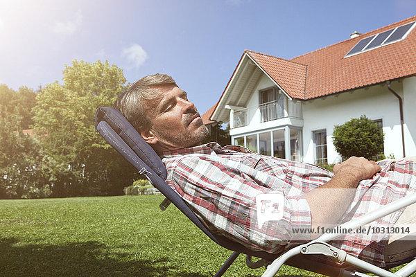 Entspannter Mann im Liegestuhl im Garten