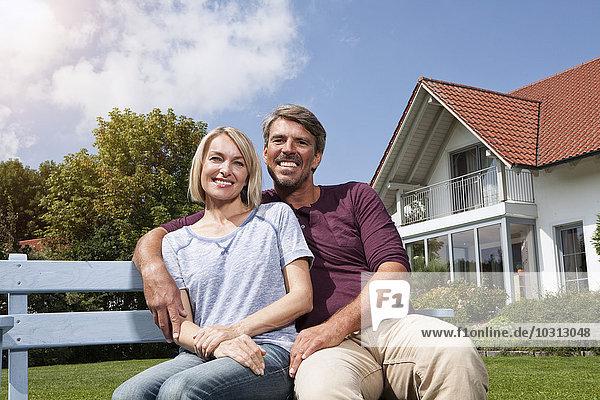 Entspanntes reifes Paar auf der Bank im Garten sitzend