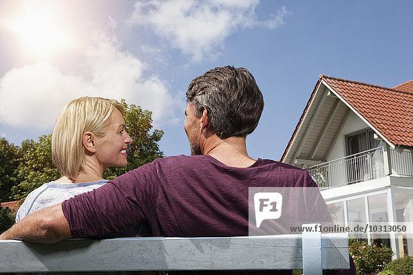 Rückansicht des reifen Paares auf der Bank im Garten
