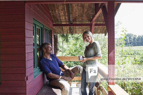 Glückliches reifes Paar auf der Veranda des Sommerhauses