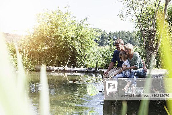 Glückliche Familie sitzend mit Dip-Netz am Steg am See