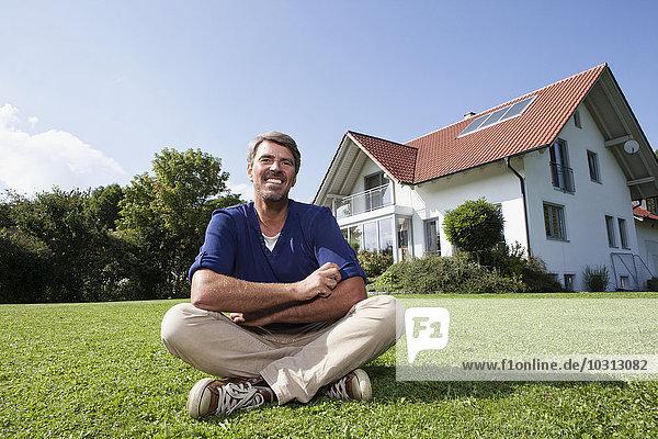Lächelnder Mann auf Rasen im Garten sitzend