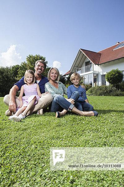 Happy family sitting on lawn in garden
