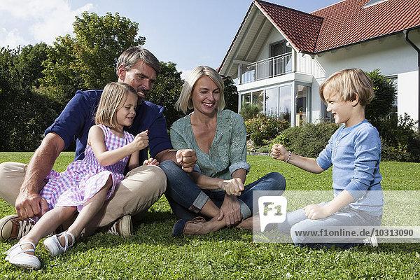 Fröhliche Familie sitzt auf Rasen im Garten und spielt Stein-Papier-Schere
