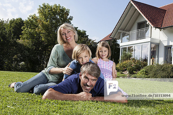 Happy family lying on lawn in garden