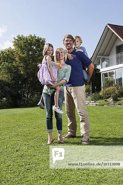 Porträt einer glücklichen Familie im Garten