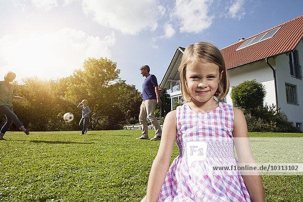Lächelndes Mädchen mit Familie beim Fußballspielen im Garten