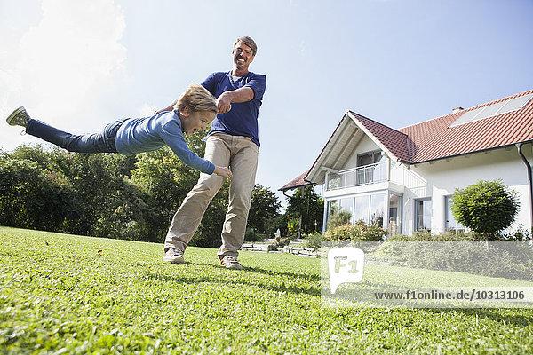 Vater spielt mit Sohn im Garten
