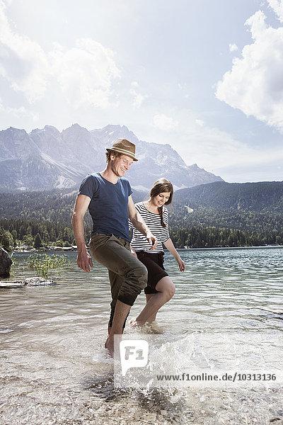 Deutschland  Bayern  Eibsee  glückliches Pärchen beim Planschen im Wasser