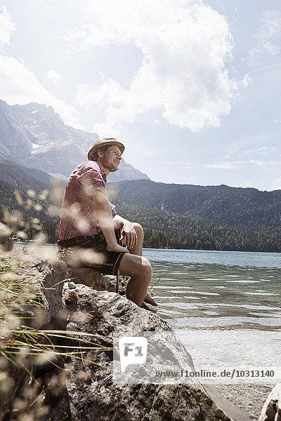 Germany  Bavaria  Eibsee  smiling man in lederhosen sitting on lakeshore