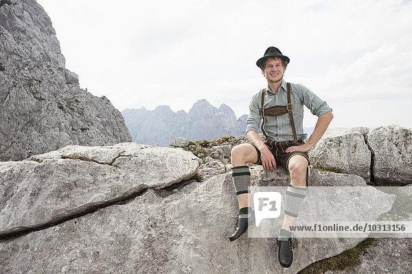 Deutschland  Bayern  Osterfelderkopf  Mann in traditioneller Kleidung sitzend in Berglandschaft