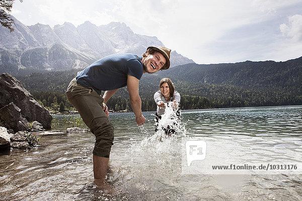 Deutschland  Bayern  Eibsee  verspieltes Pärchen beim Planschen im Wasser