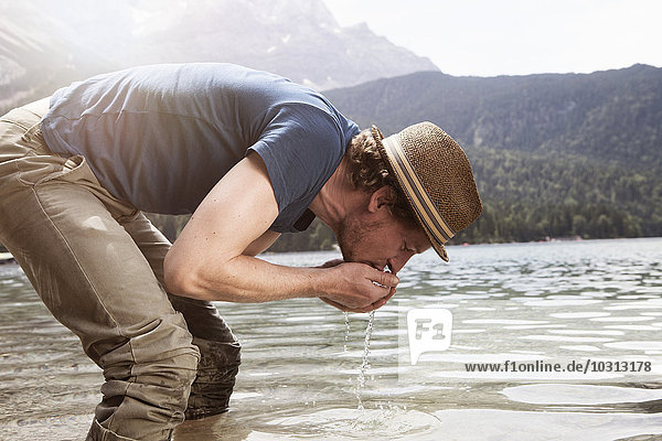 Deutschland  Bayern  Eibsee  Mann Trinkwasser aus dem See Deutschland, Bayern, Eibsee, Mann Trinkwasser aus dem See