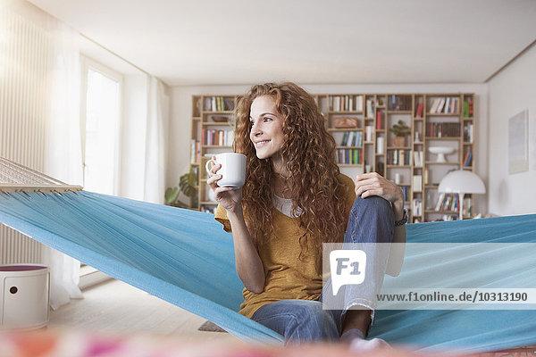 Lächelnde Frau zu Hause sitzend in der Hängematte mit Tasse Kaffee