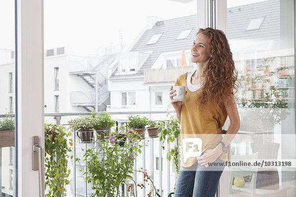 Lächelnde Frau mit einer Tasse Kaffee gegen die Balkontür gelehnt