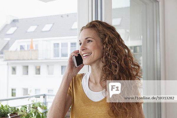 Lächelnde Frau zu Hause am Telefon