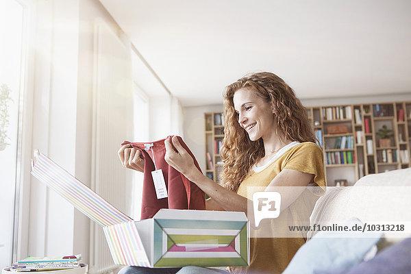 Lächelnde Frau zu Hause auf der Couch sitzend  Paket mit Kleidungsstück auspackend