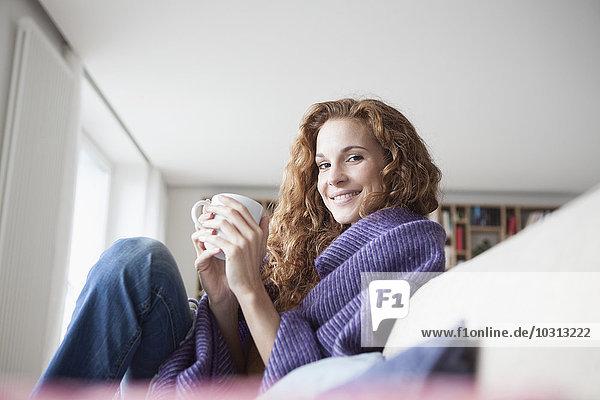 Lächelnde Frau zu Hause auf der Couch sitzend  Tasse haltend