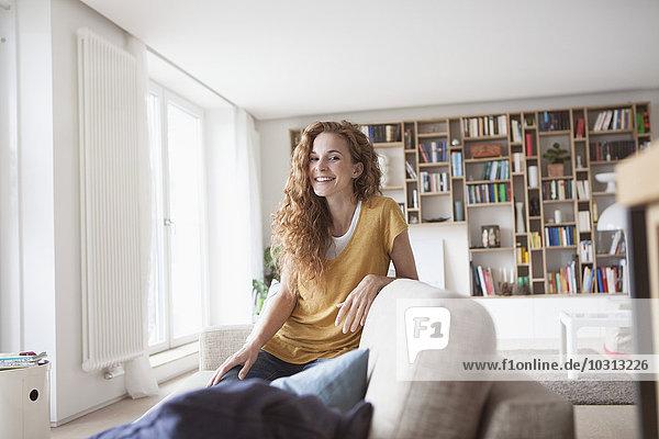 Lächelnde Frau zu Hause kniend auf der Couch