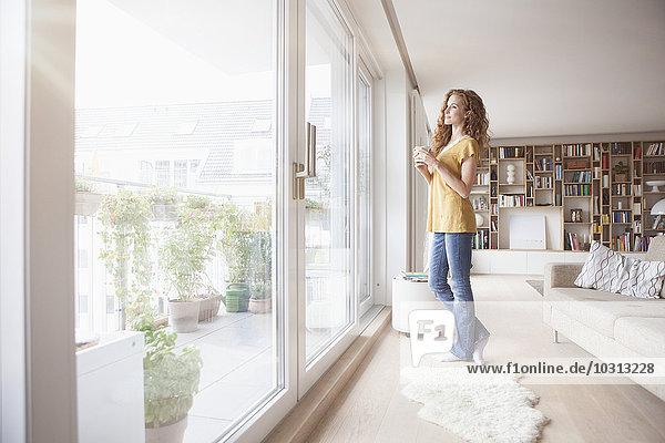Frau zu Hause aus dem Fenster schauend