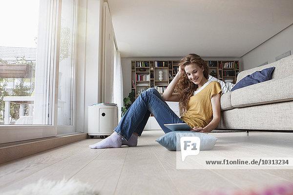 Frau zu Hause sitzend auf dem Boden mit digitalem Tablett