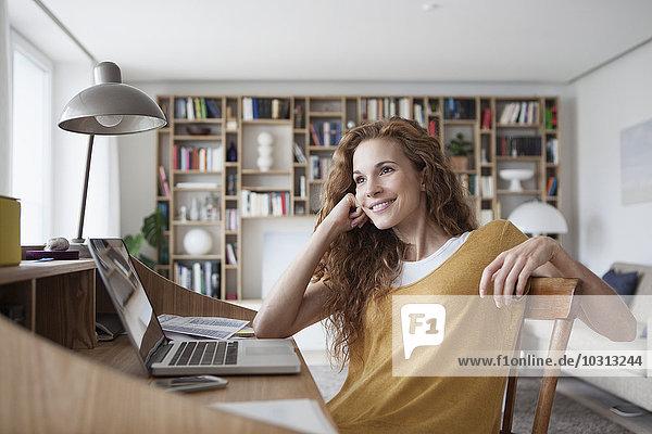 Lächelnde Frau zu Hause mit Laptop auf dem Sekretärinnenschreibtisch