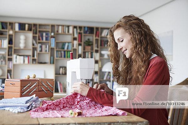 Lächelnde Frau zu Hause mit der Nähmaschine