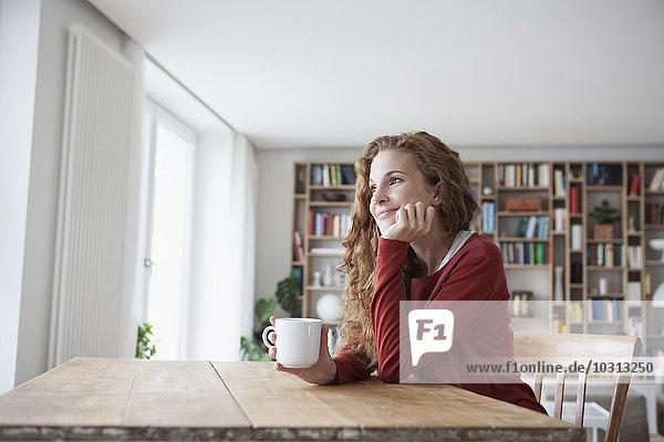Lächelnde Frau zu Hause sitzend am Holztisch mit Tasse
