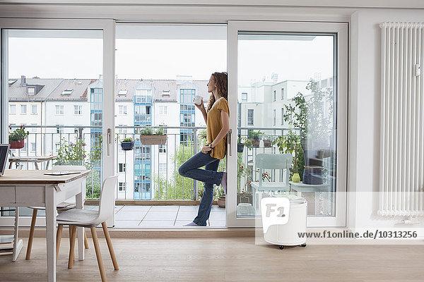 Frau mit Tasse Kaffee gegen die Balkontür gelehnt