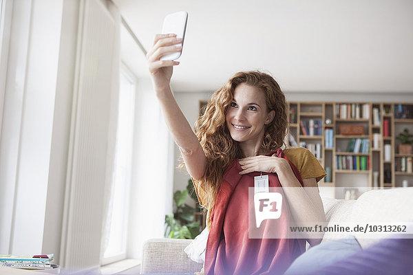 Lächelnde Frau zu Hause  die einen Selfie mit neuem Kleidungsstück mitnimmt.
