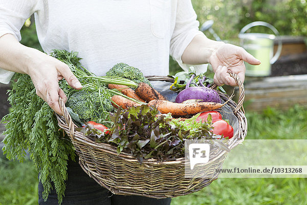 Mann hält Korb mit gemischtem Gemüse