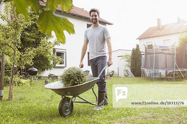 Mann schiebt Schubkarre mit Pflanze im Garten