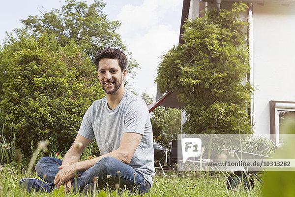 Lächelnder Mann im Garten sitzend