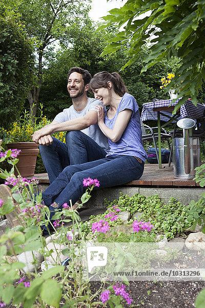 Glückliches Paar sitzt auf der Gartenterrasse