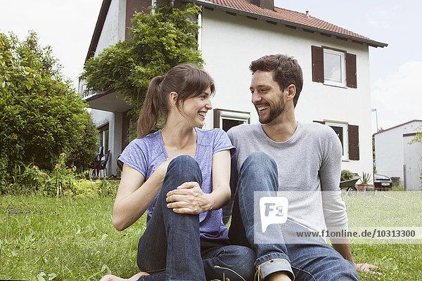 Lächelndes Paar im Garten sitzend