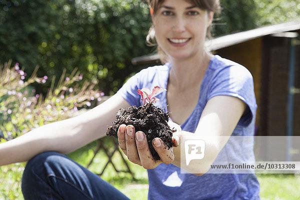 Lächelnde Frau im Garten hält Erde mit Setzling